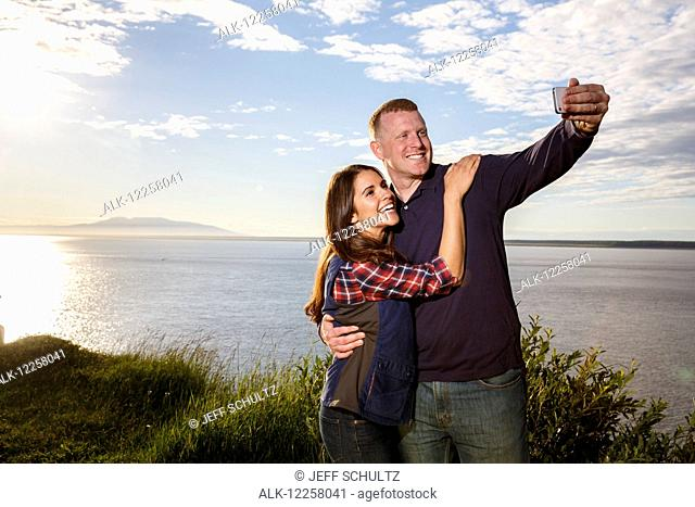 Young couple using a smart photo to take a selfie at sunset, Point Woronzof, Anchorage, Southcentral Alaska, Summer
