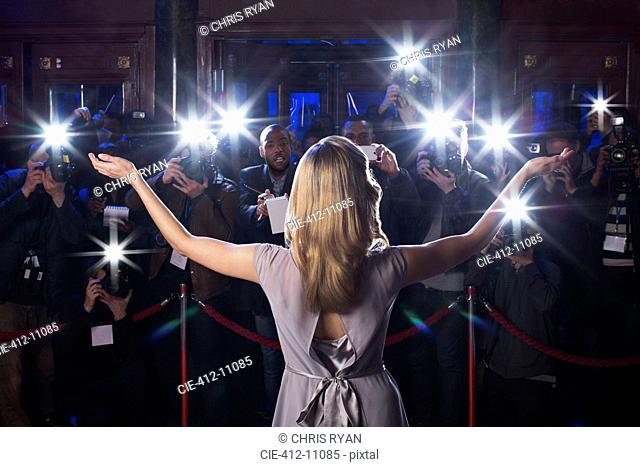 Rear view of female celebrity with arms outstretched to paparazzi at red carpet event