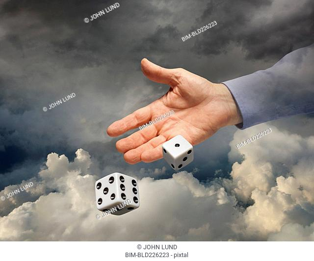Hand of Caucasian businessman rolling dice in sky