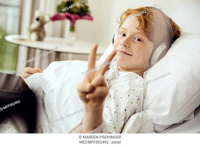 Sick boy lying in hospital making victory sign, wearing head phones