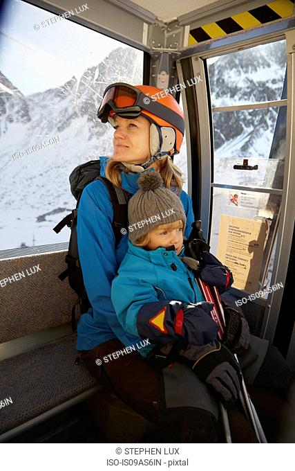 Mature female skier and toddler son sitting in ski lift, Neustift, Stubaital, Tirol, Austria