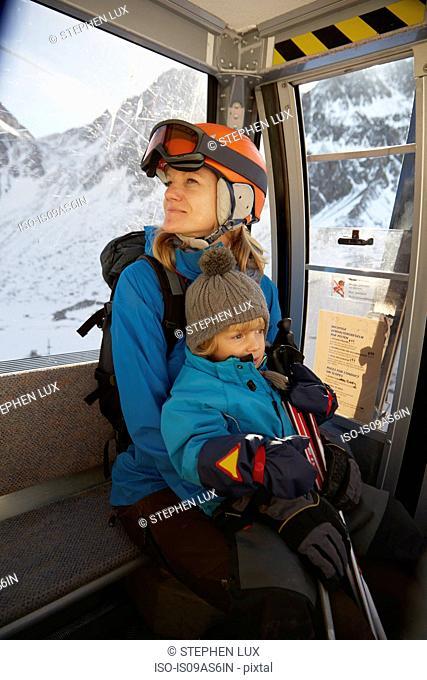 Mature female skier and toddler son sitting in ski lift, Neustift, Stubaital, Tirol, Austria