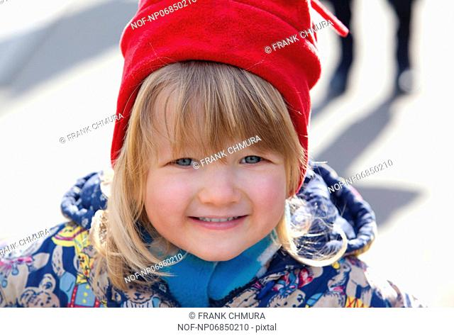 portrait of a smiling boy with long blond hair and red hat