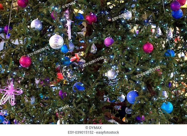 Toys and lights on dressed up Christmas tree as background closeup
