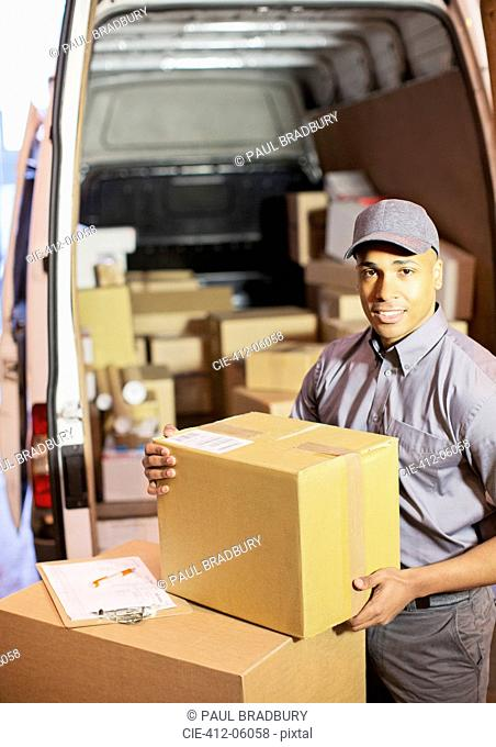 Delivery boy loading boxes into van