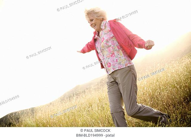 Caucasian woman running down hill
