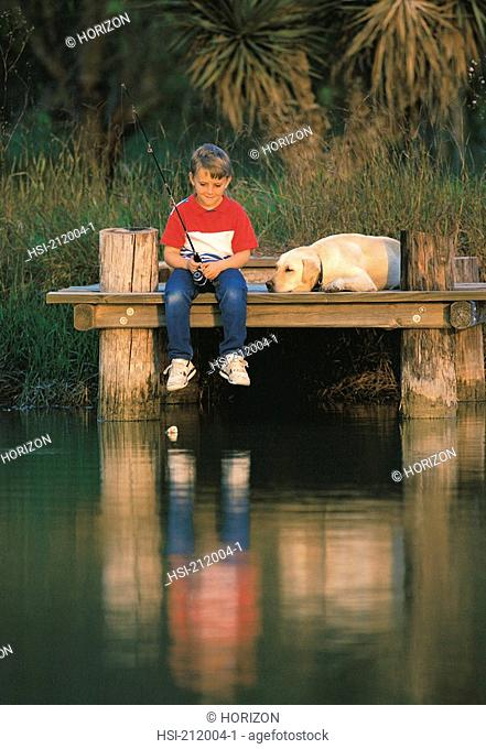 Boy fishing from dock with dog