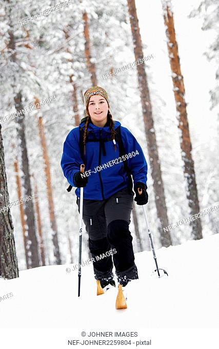 Young woman skiing in winter forest