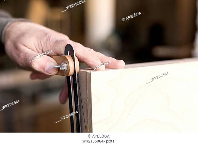 Close-up of carpenter's hands measuring wood in workshop