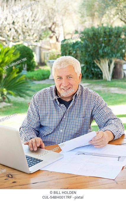 Older man paying bills on laptop