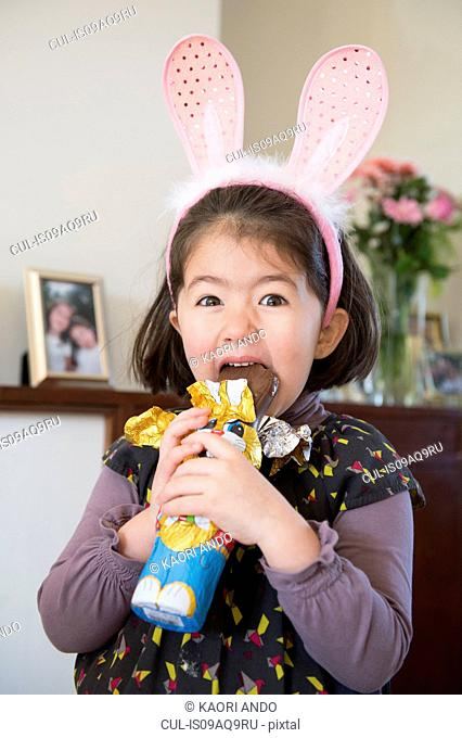 Young girl wearing bunny ears, just about to bite into chocolate bunny