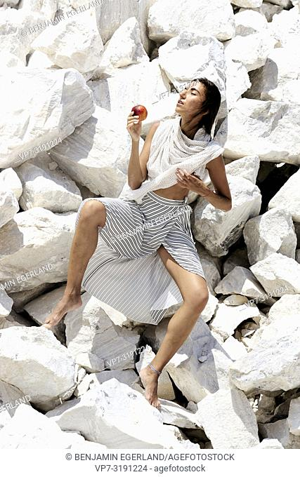 Woman on rocks with apple
