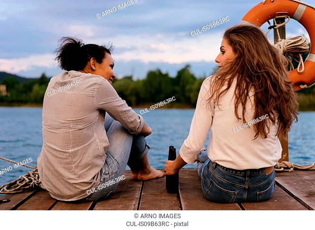 Two women, relaxing on pier, hold bottles of beer, rear view