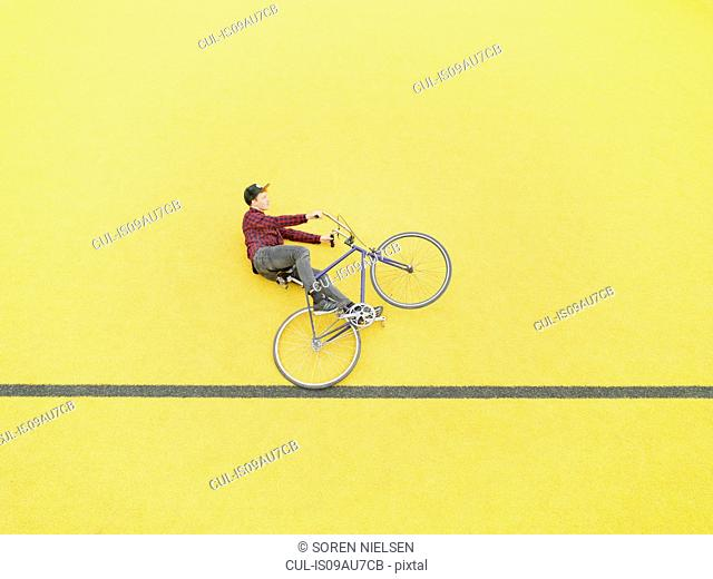Urban cyclist doing illusionary stunt against yellow wall