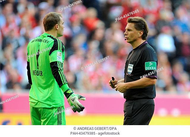 Munich's goalkeeper Manuel Neuer (L) speaks with referee Thorsten Kinhoefer during the German Bundesliga soccer match between FC Bayern Munich and FSV Mainz 05...