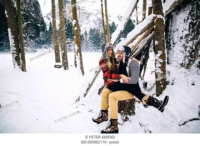 Woman sitting on mans lap in snow-covered landscape