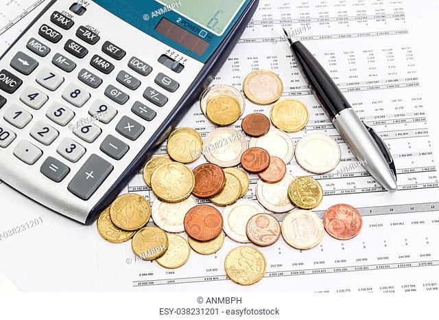 Several euro coins from 1 cents to 2 euro scattered on the printed table with data, pen and fragment of a calculator