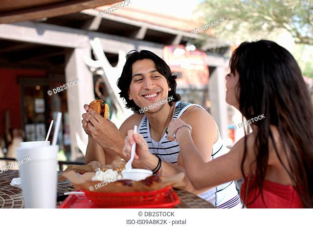 Young couple eating in outdoor cafe, smiling