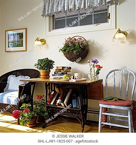 PORCHES enclosed three season porch, natural wicker table and chair, wall sconces, books stacked, coffe mug, terra cotta pots of geraniums