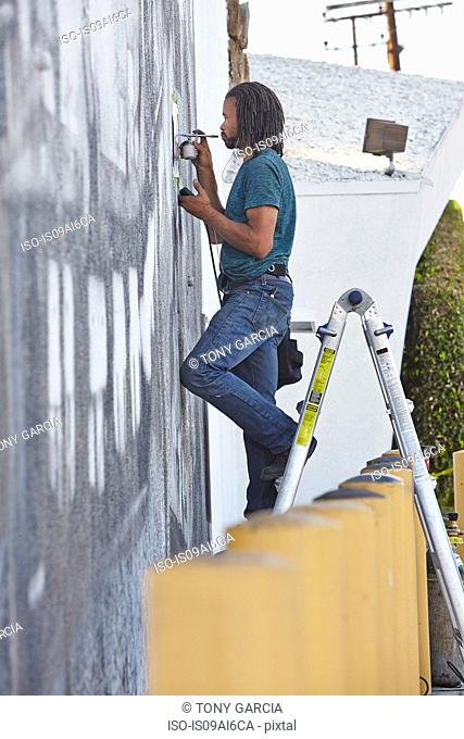 Male african american airbrush artist on step ladders painting mural