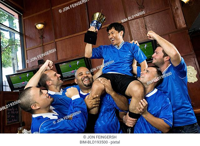 Cheering teammates lifting man holding trophy