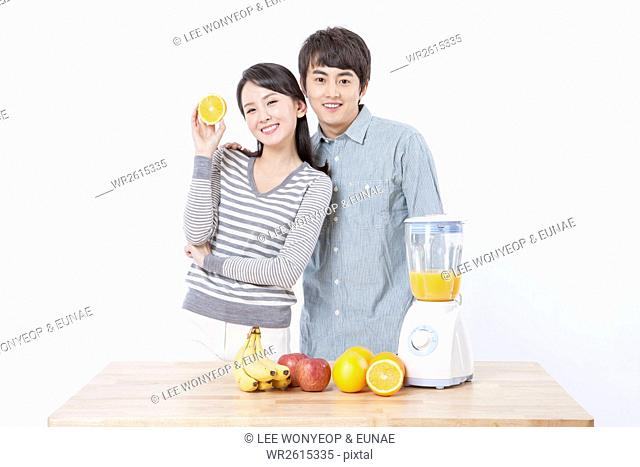 Young smiling couple making fruit juice