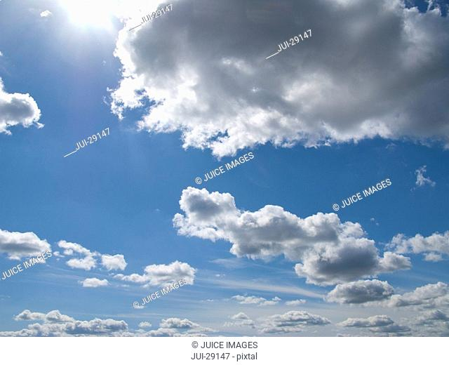 Sun and clouds floating in blue sky