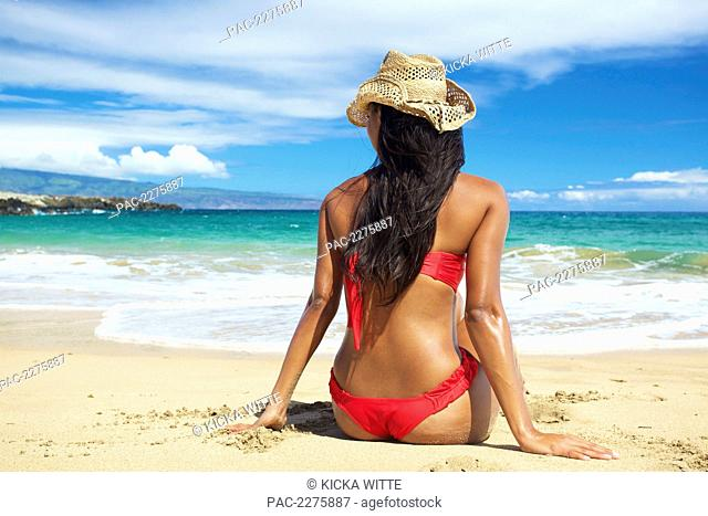 A young woman in a red bikini sitting on the beach of an hawaiian island; Maui, Hawaii, United States of America