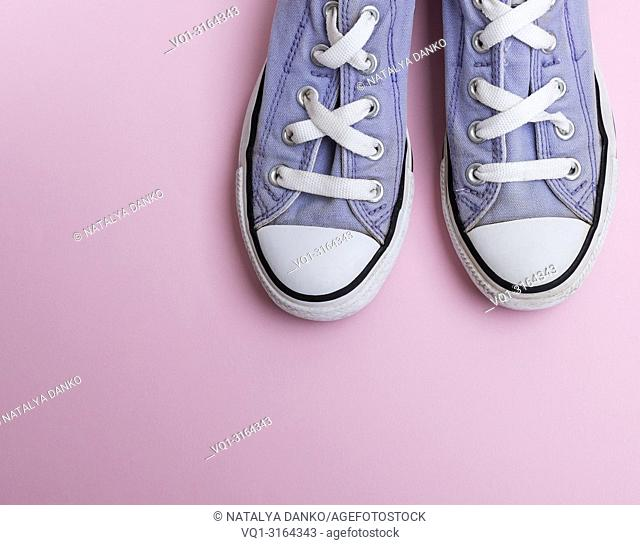 pair of old worn purple sneakers with white laces on a pink background, top view, copy space