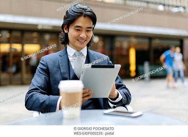 USA, New York City, smiling businessman at outdoor cafe looking at digital tablet