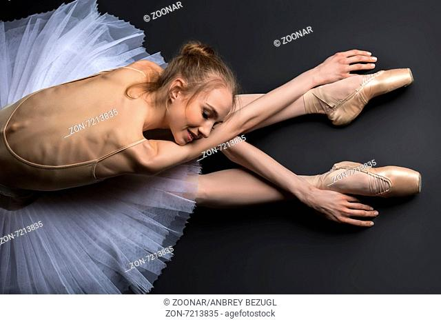 Young, graceful ballerina sitting on the floor on a black background in a studio in the slope face touching knees