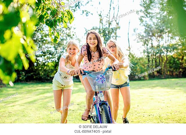 Girls cycling in garden