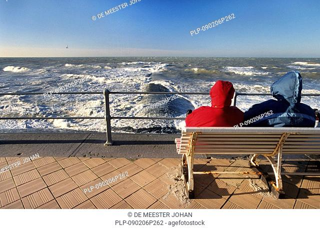 Tourists on bench on sea dyke looking at the waves and breakwater in winter, Ostend, Belgium