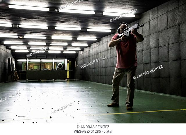 Man aiming with a tactical weapon in an indoor shooting range
