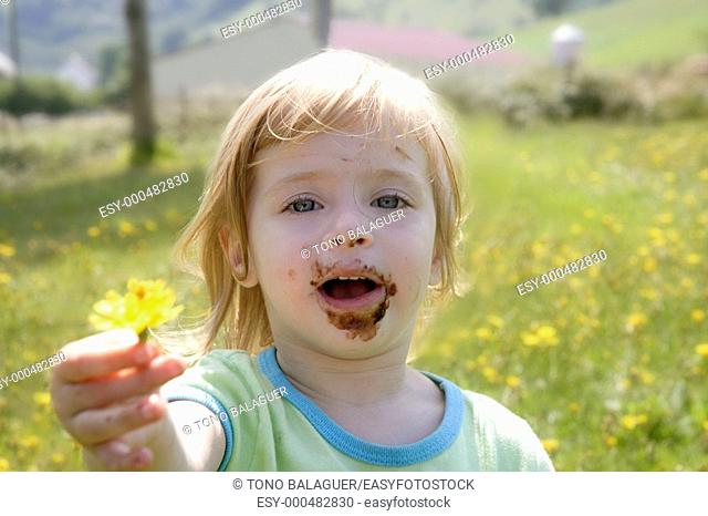 Adorable little girl eating chocolate outdoor field