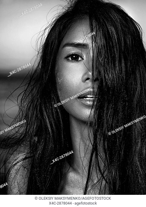 Sensual black and white beauty portrait of a young woman exotic mixed-race ethnicity face with long dark hair and sand particles on her hair and skin