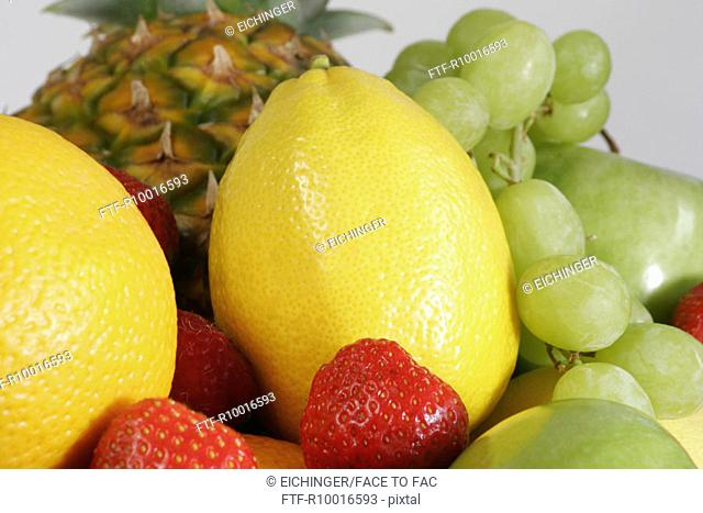 A variety of lemon, strawberries, grapes, apples and pineapple seen together