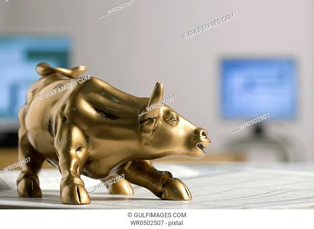 Bull figurine on newspaper, background computers, close-up