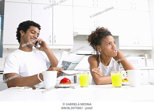 Frustrated African woman in kitchen with boyfriend