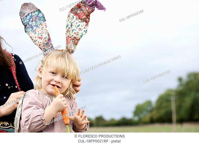 Little girl nibbling with bunny ears