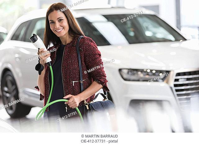 Portrait smiling, confident woman holding hybrid charging cable in car dealership showroom
