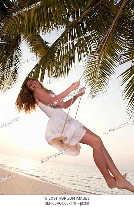 Woman swinging on tropical beach