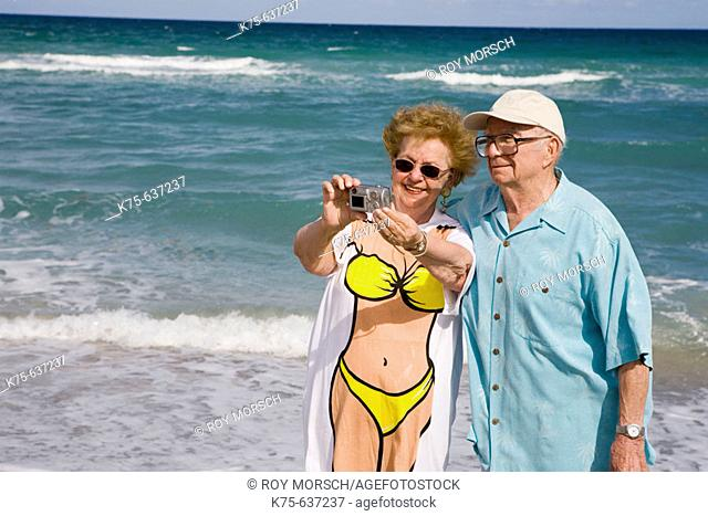 Senior couple taking picture of themselves at beach