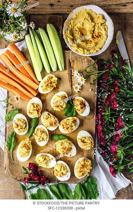 Hummus deviled eggs are served on a wooden board with cucumber and carrot sticks, arugula, and flowers