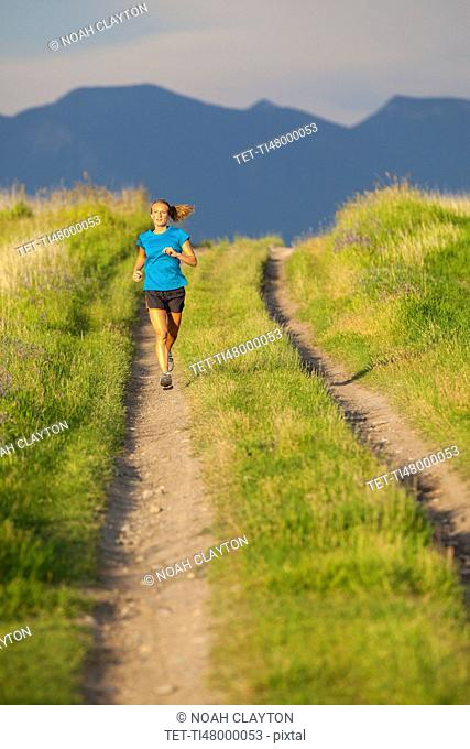 Front view of young woman jogging