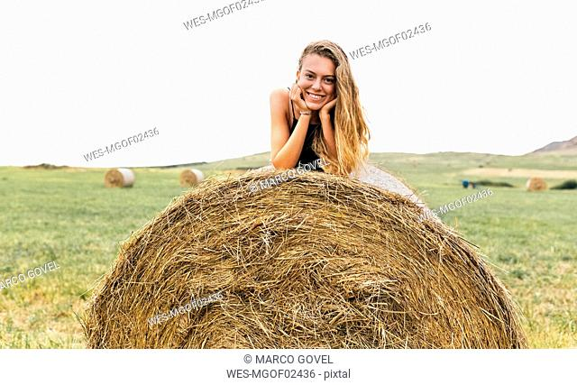 Portrait of smiling blond teenage girl lying on straw bale