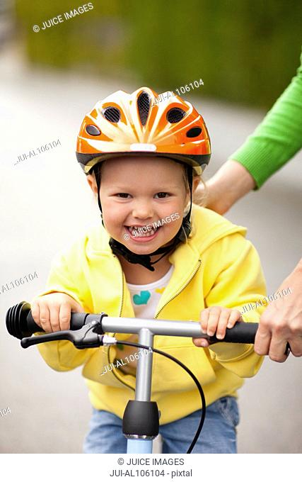 Young girl learning how to ride a bike with mother