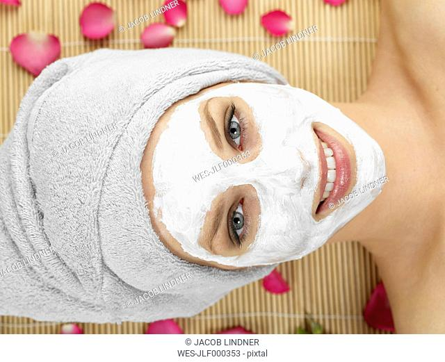 Young woman with face mask at spa, smiling, portrait