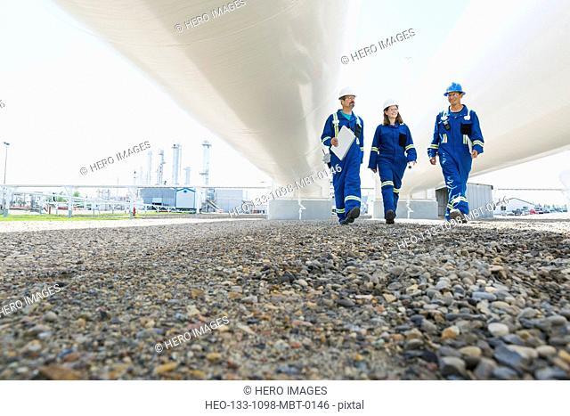 Workers walking below tanks at gas plant