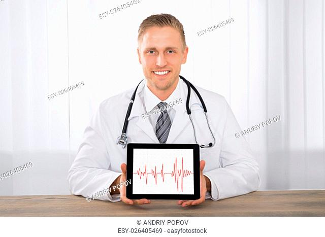 Close-up Of Young Happy Male Doctor Showing Heartbeat On Digital Tablet At Desk In Clinic